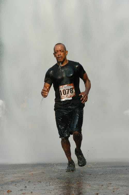 Man in Black Running Under Rain