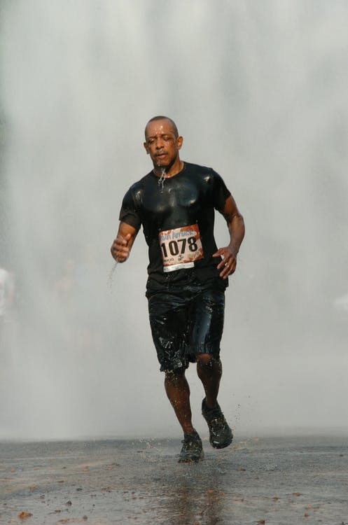 Man in Black Running Under Rain