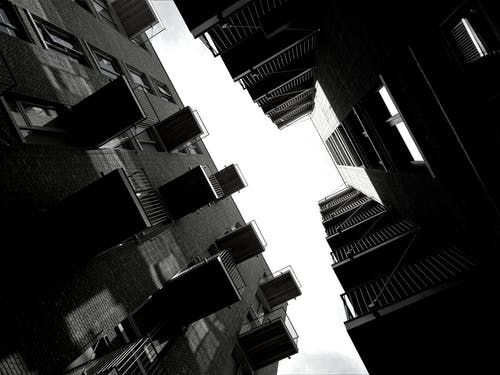 Grayscale and Low-angle Photography Two High-rise Buildings