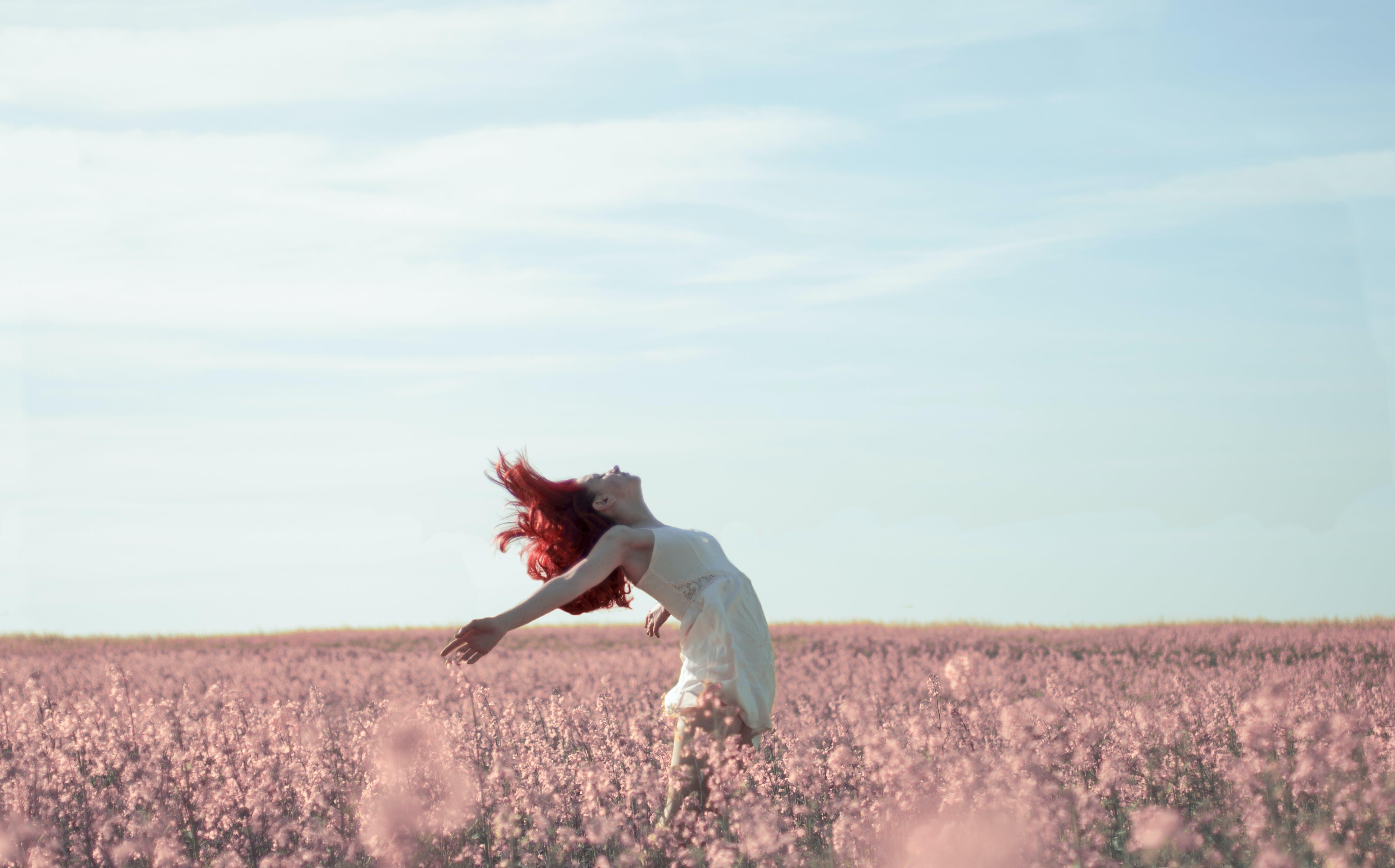 Woman in Yellow Dress Standing on Pink Petaled Flower Field