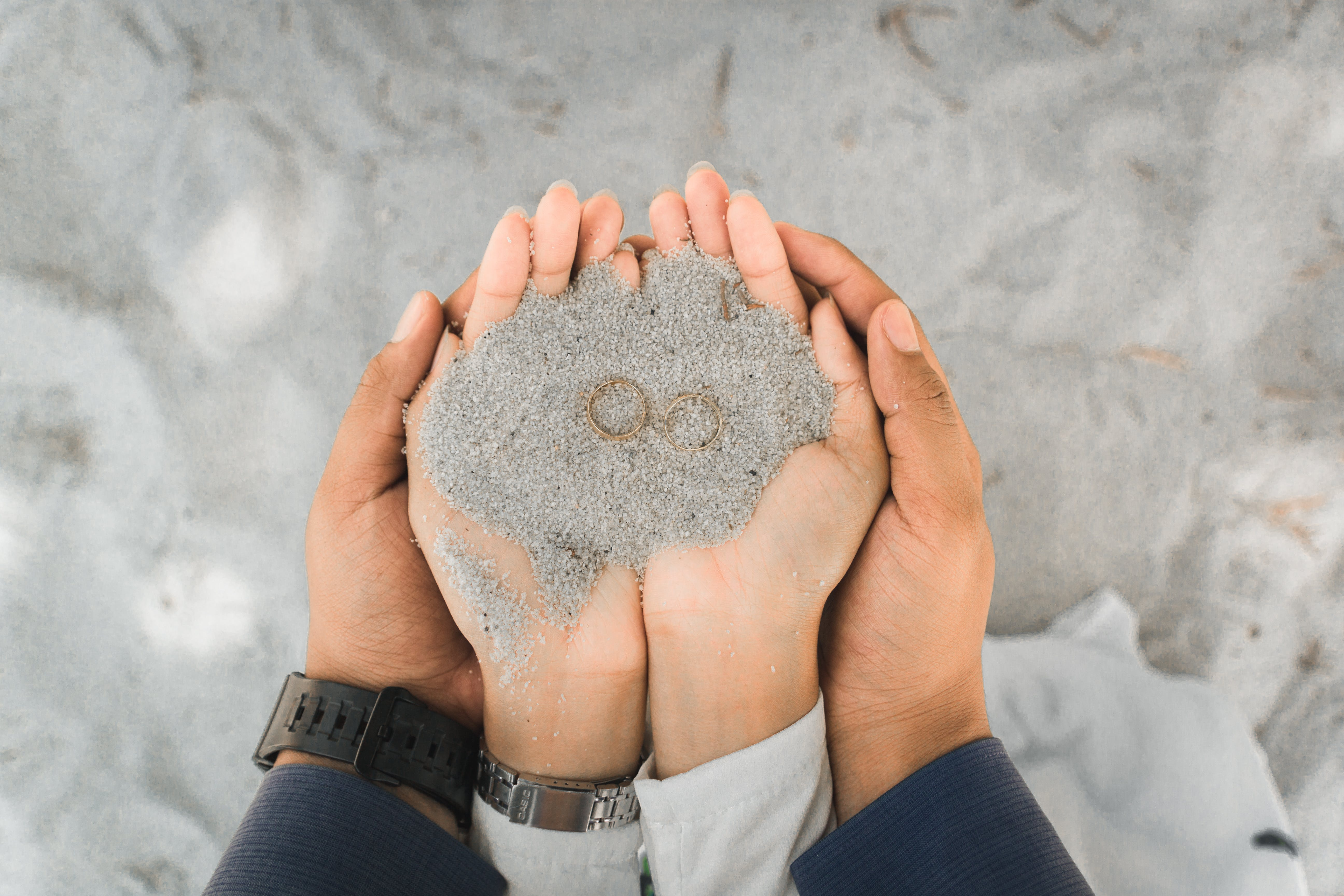 Two Person's Hands Holding a Sand
