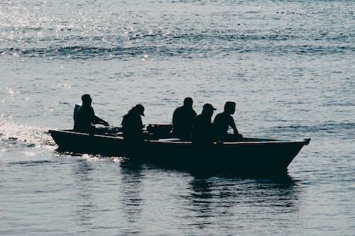 bir teknede halkların silüeti içeren Ücretsiz stok fotoğraf