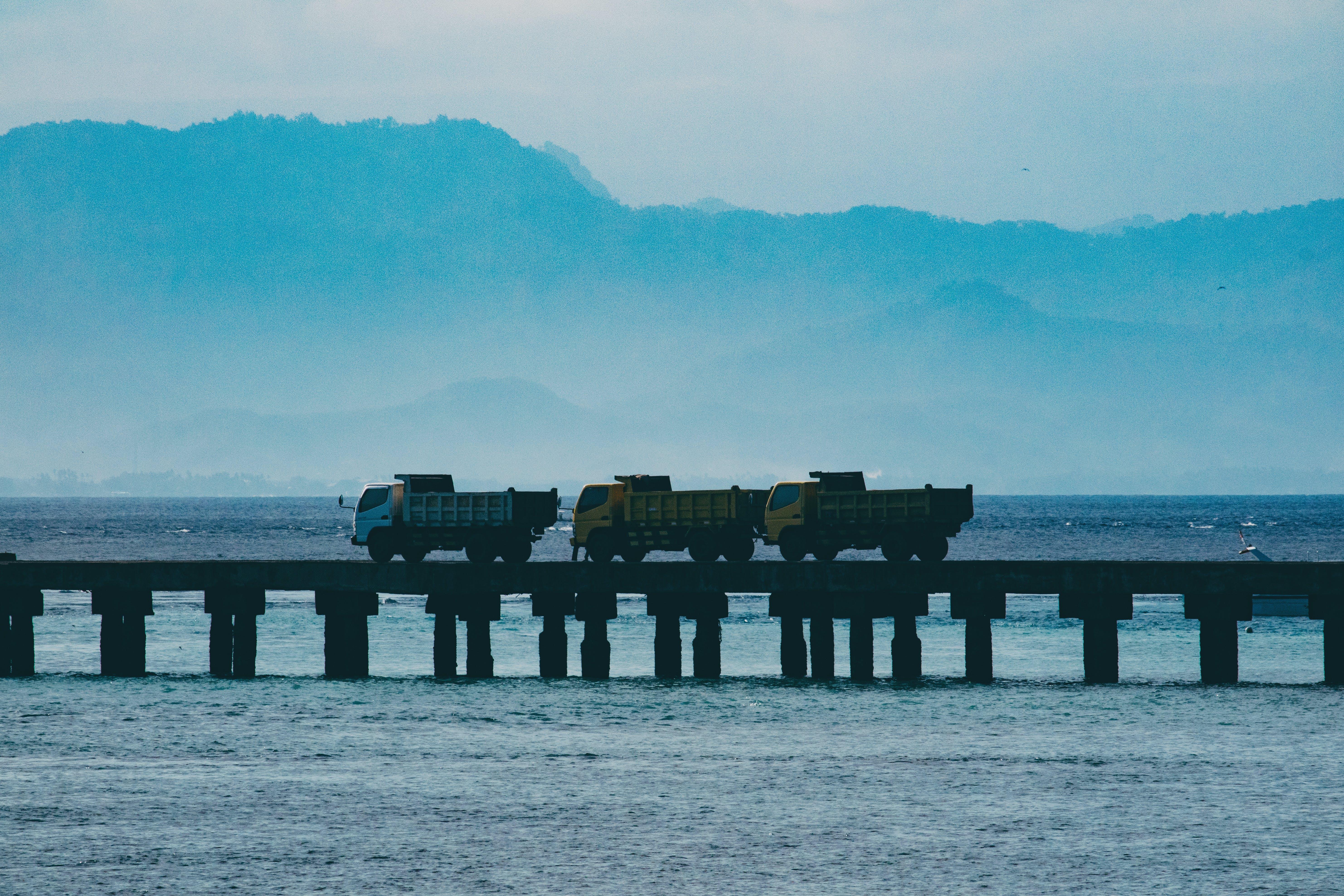 Kostenloses Stock Foto zu lkws über eine brücke im hafen