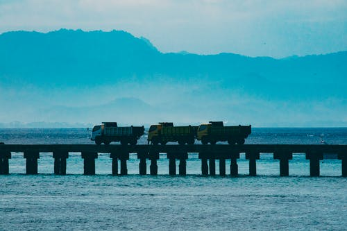 Free stock photo of trucks crossing a bridge in the harbour