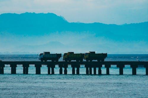 항구에서 다리를 건너는 트럭의 무료 스톡 사진