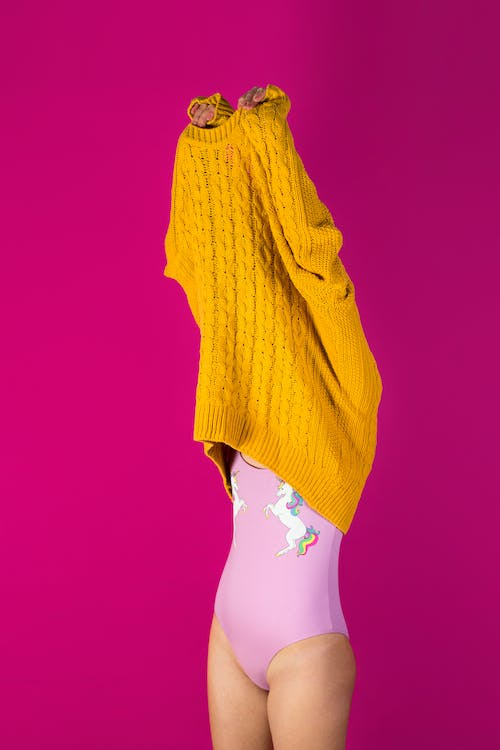 Photo of Woman About to Wear Off Yellow Sweater in Pink Background