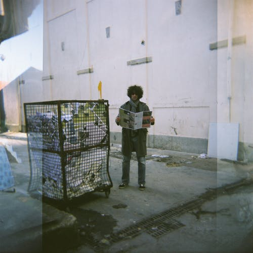 Boy in Black Jacket Standing on Gray Concrete Floor