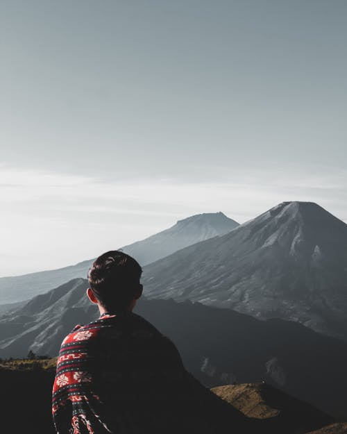 Photo of Person Atop Mountains