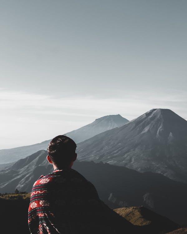 Photo of Person Atop Mountains