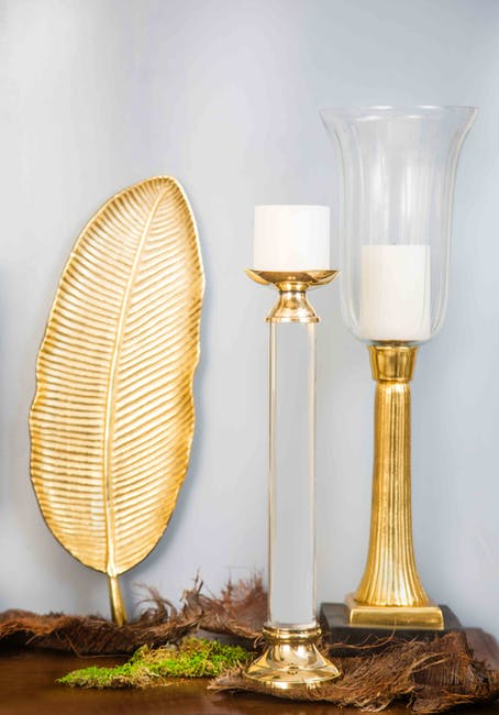 Two white pillar candles and two gold colored candlesticks
