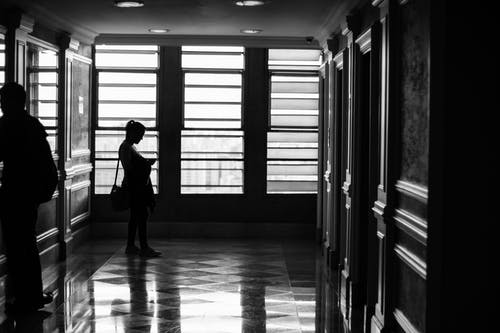 Silhouette Photography of Person Standing Near Window