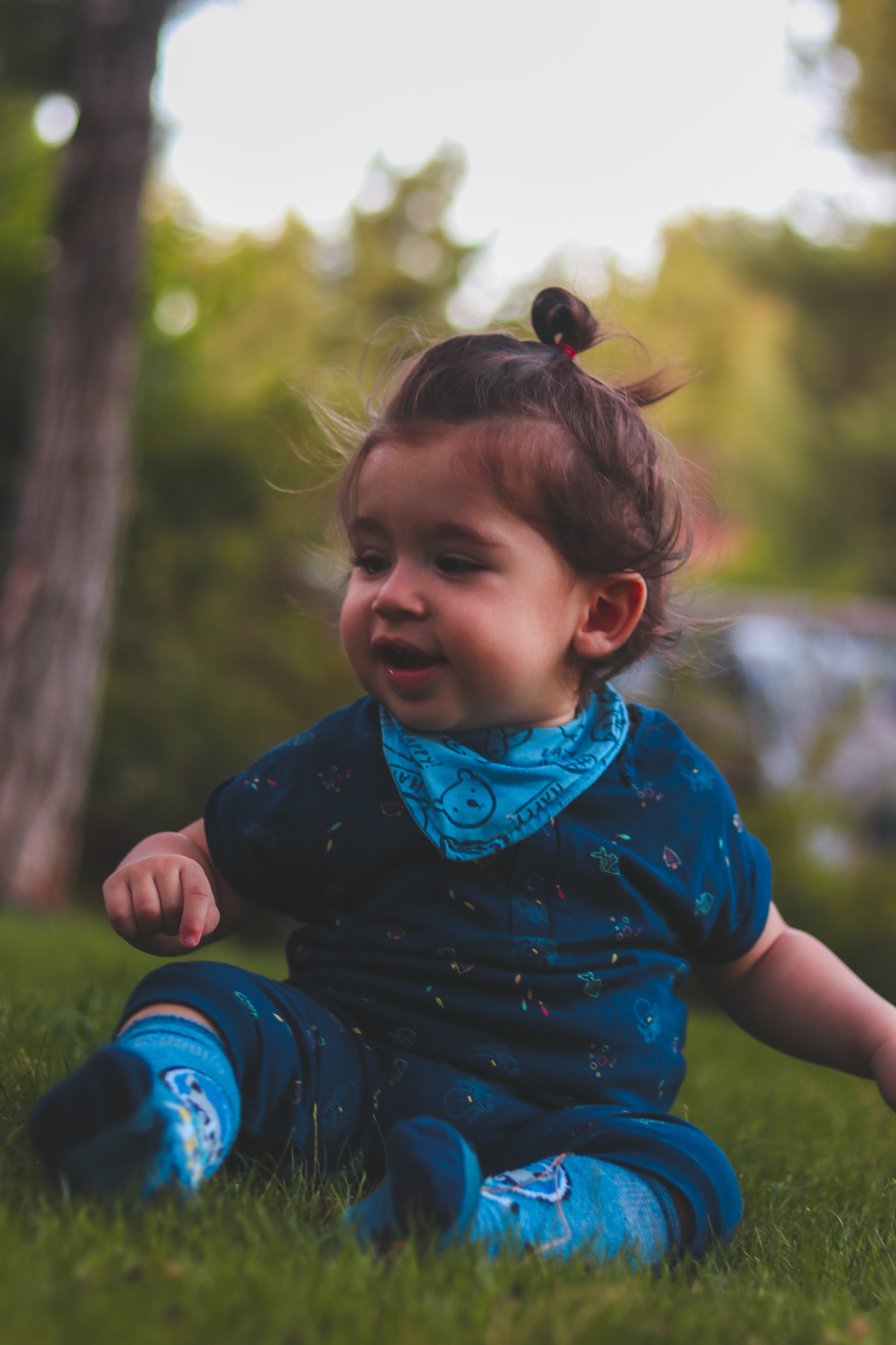 Photo of Baby Wearing Blue Onesie and Socks Sitting on Green Grass