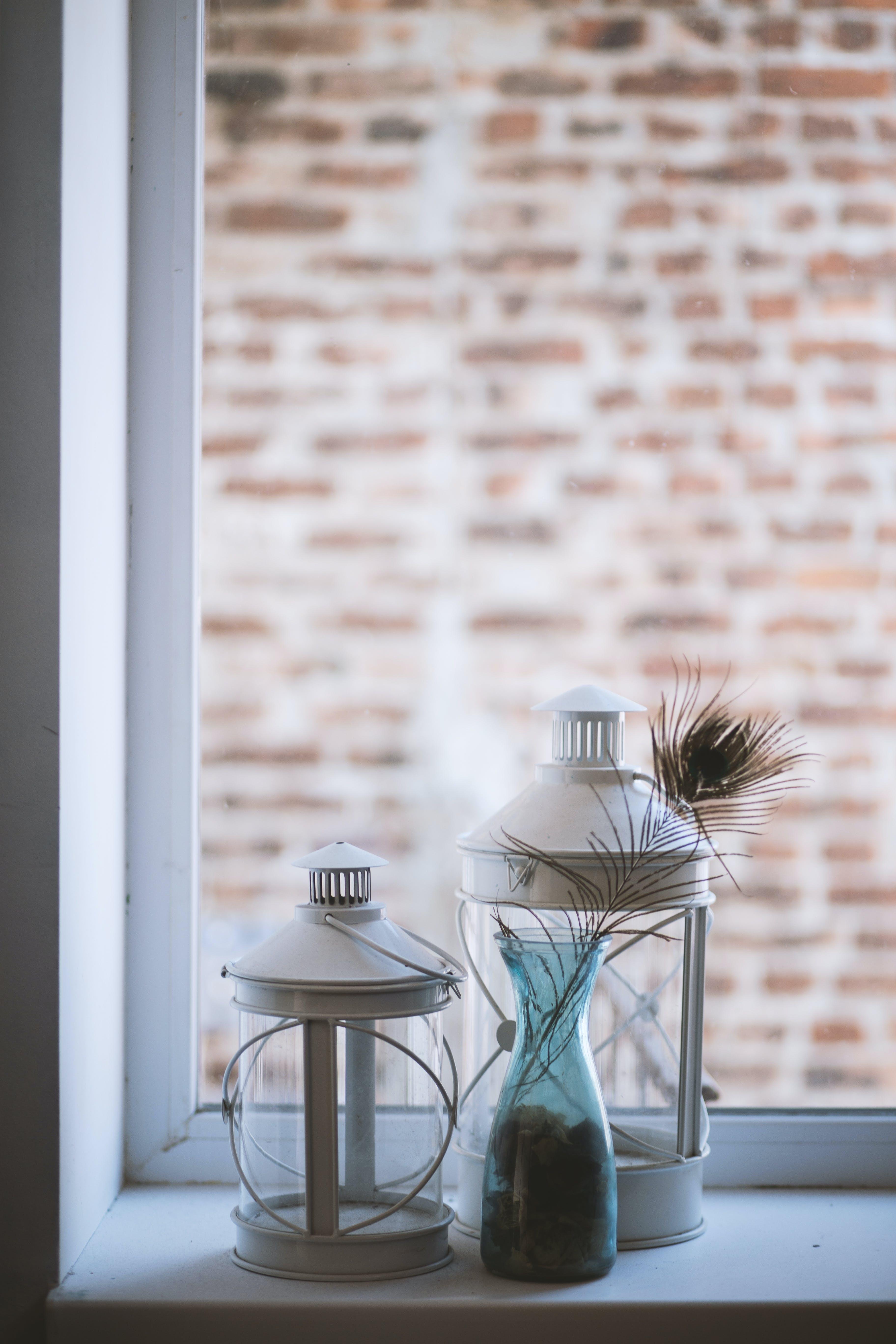 Two Clear Glass Lamp Lanterns Near Window