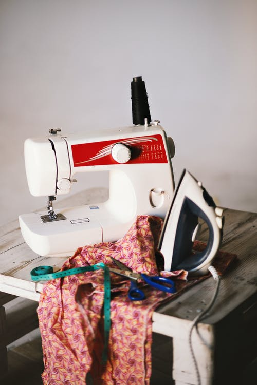 White Sewing Machine, Clothes Iron, and Scissors