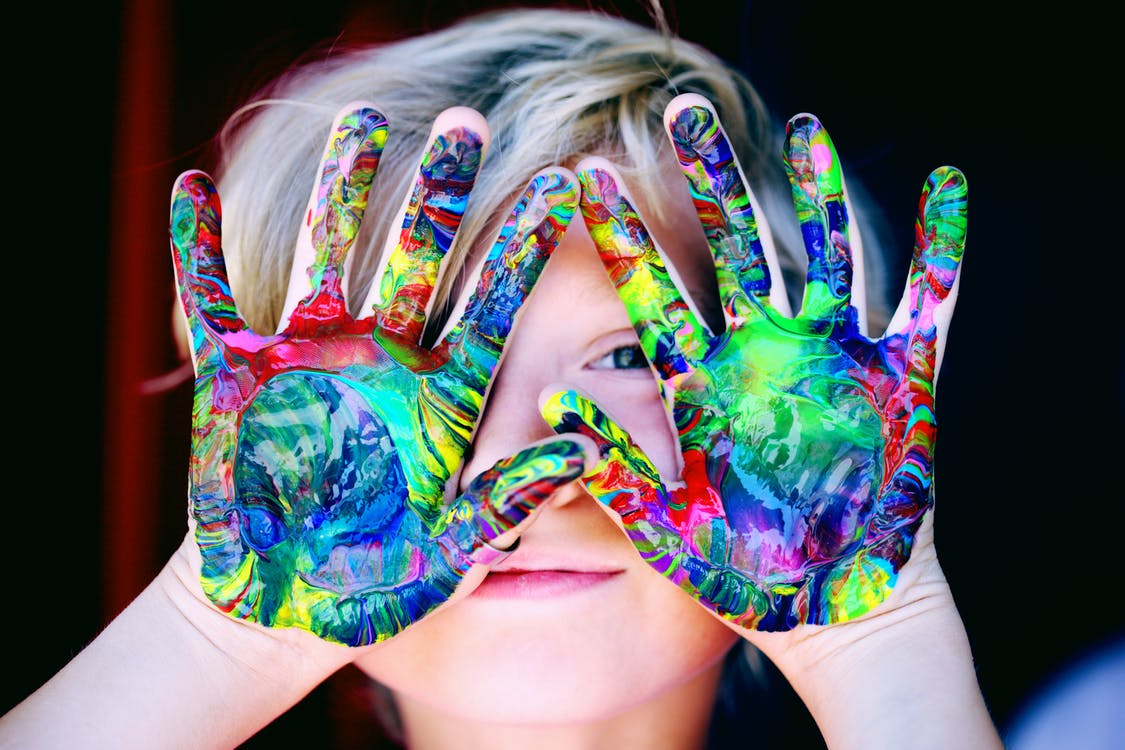 Child With Multicolored Hand Paint