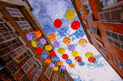 Assorted-color Umbrellas Hanged Near Brown Building