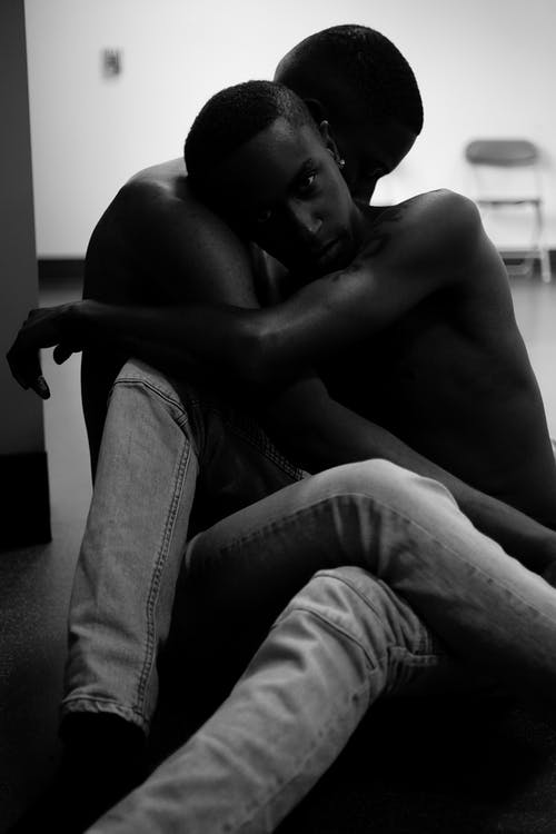 Grayscale Photo of Two Person Sitting on Floor