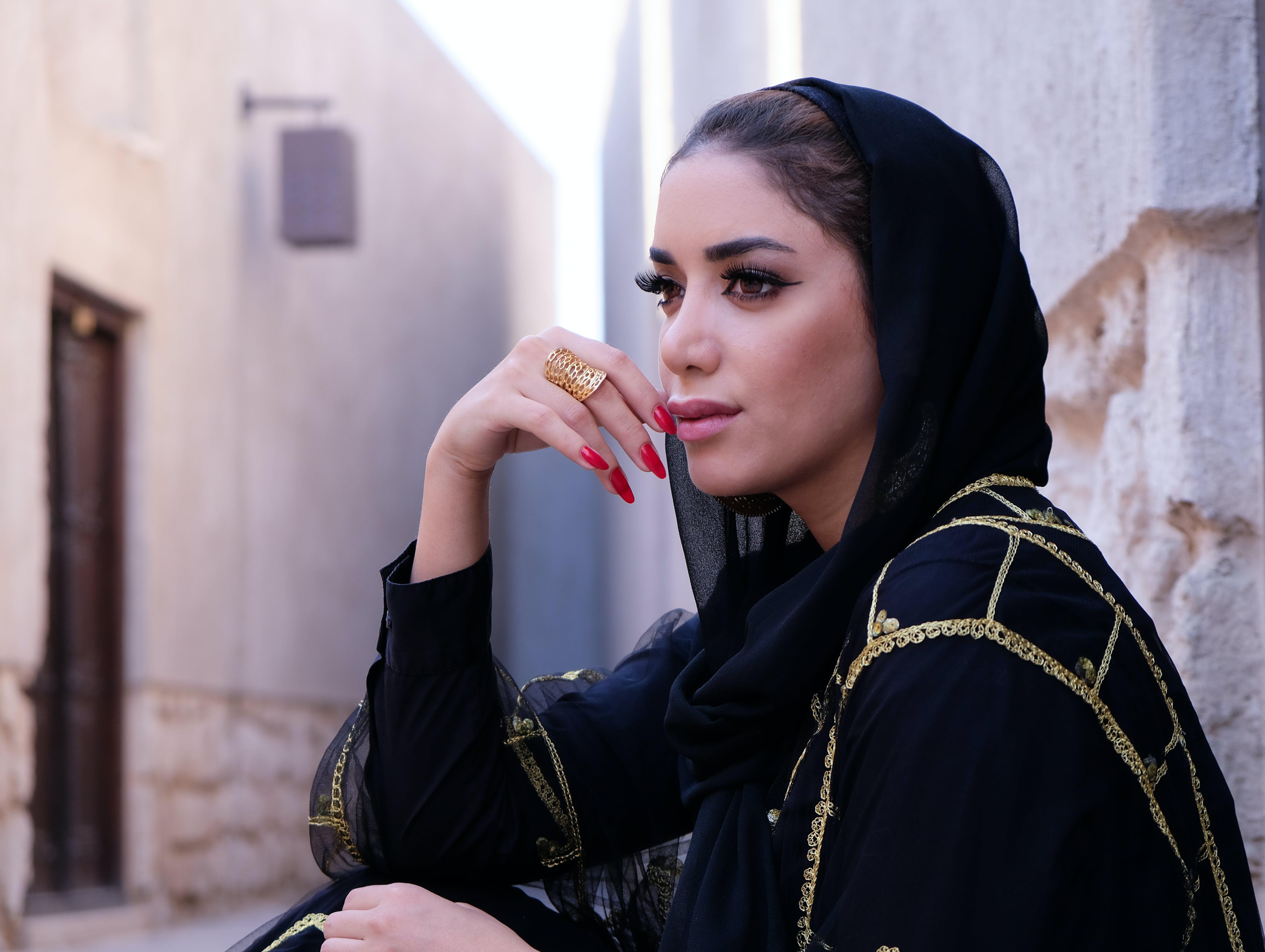 Closeup Photo of Woman Wearing Black Hijab Headdress Holding Her Lips