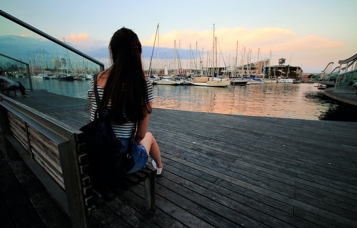 Woman in Black and White Stripe Scoop Neck Shirt Sitting on Brown Wooden Bench in Ship Dock during Daytime
