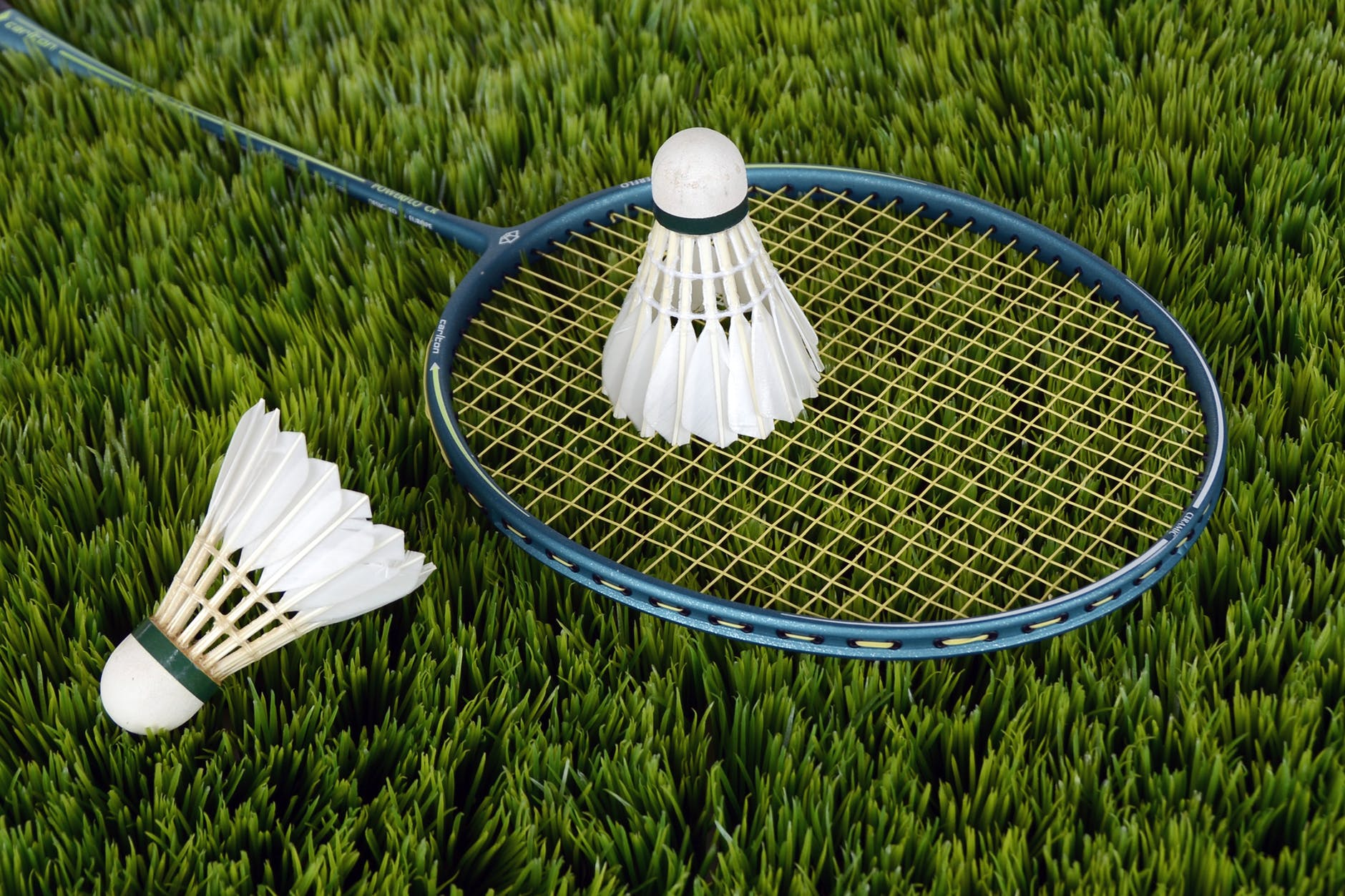 badminton racket and shuttle cocks  lying in the ground