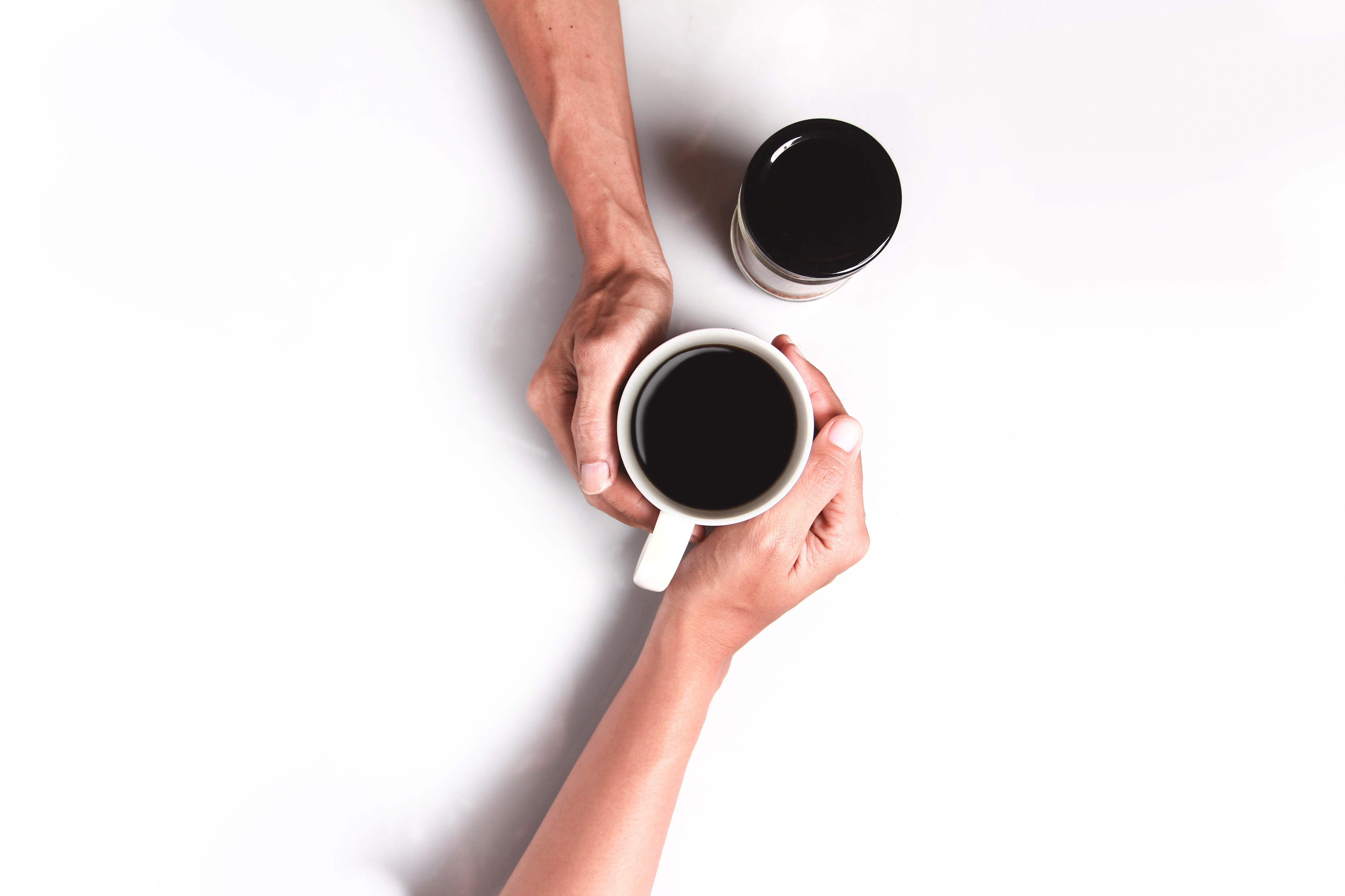 Two Person's Hand Holding White Mug Filled With Coffee