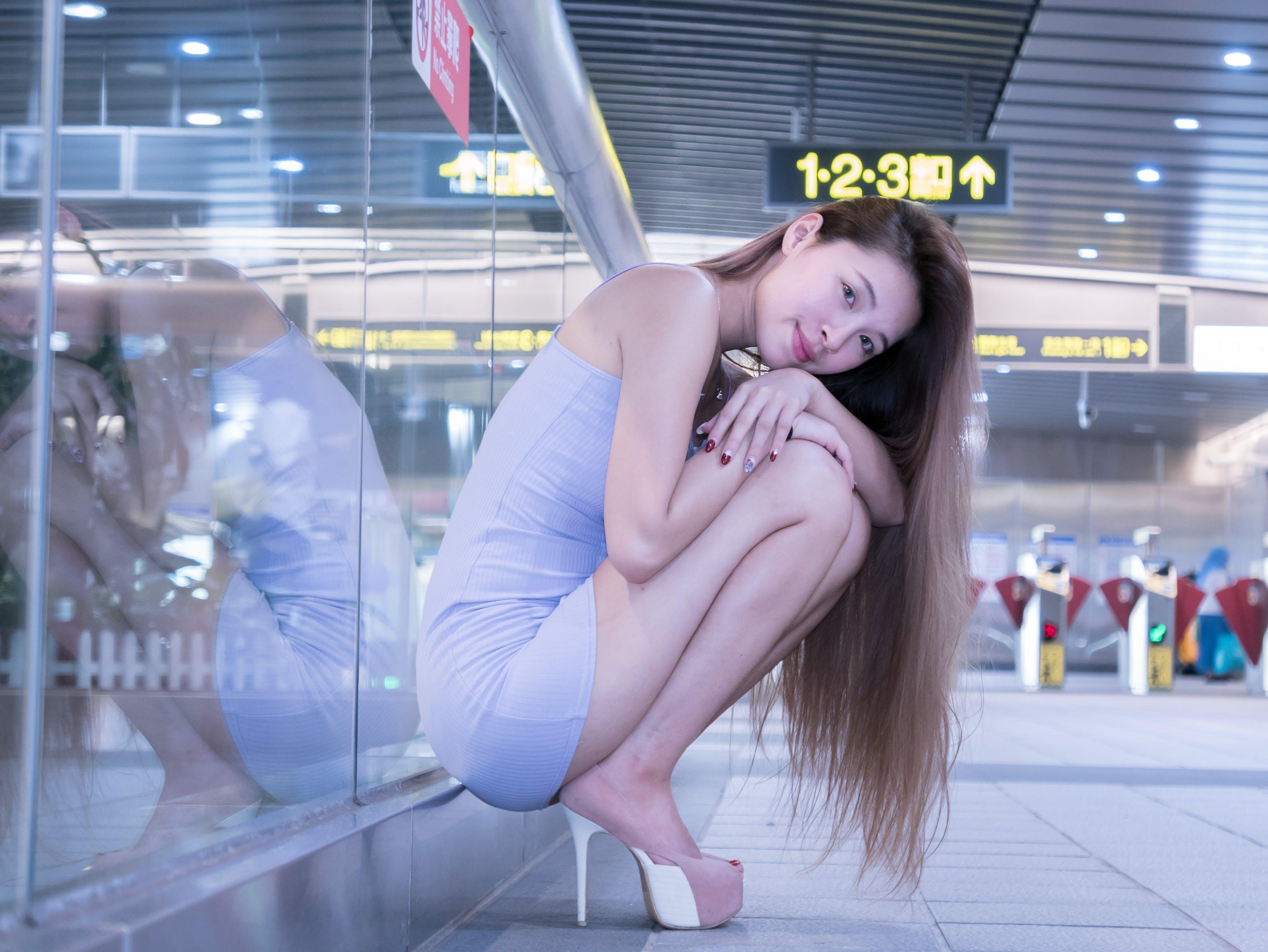 Woman Wearing Mini Dress Sitting Near Glass Wall