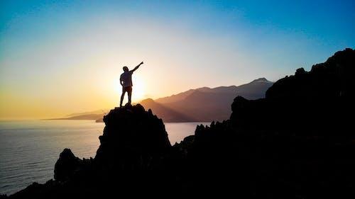Ilmainen kuvapankkikuva tunnisteilla auringonlasku, kivet, meri, mies