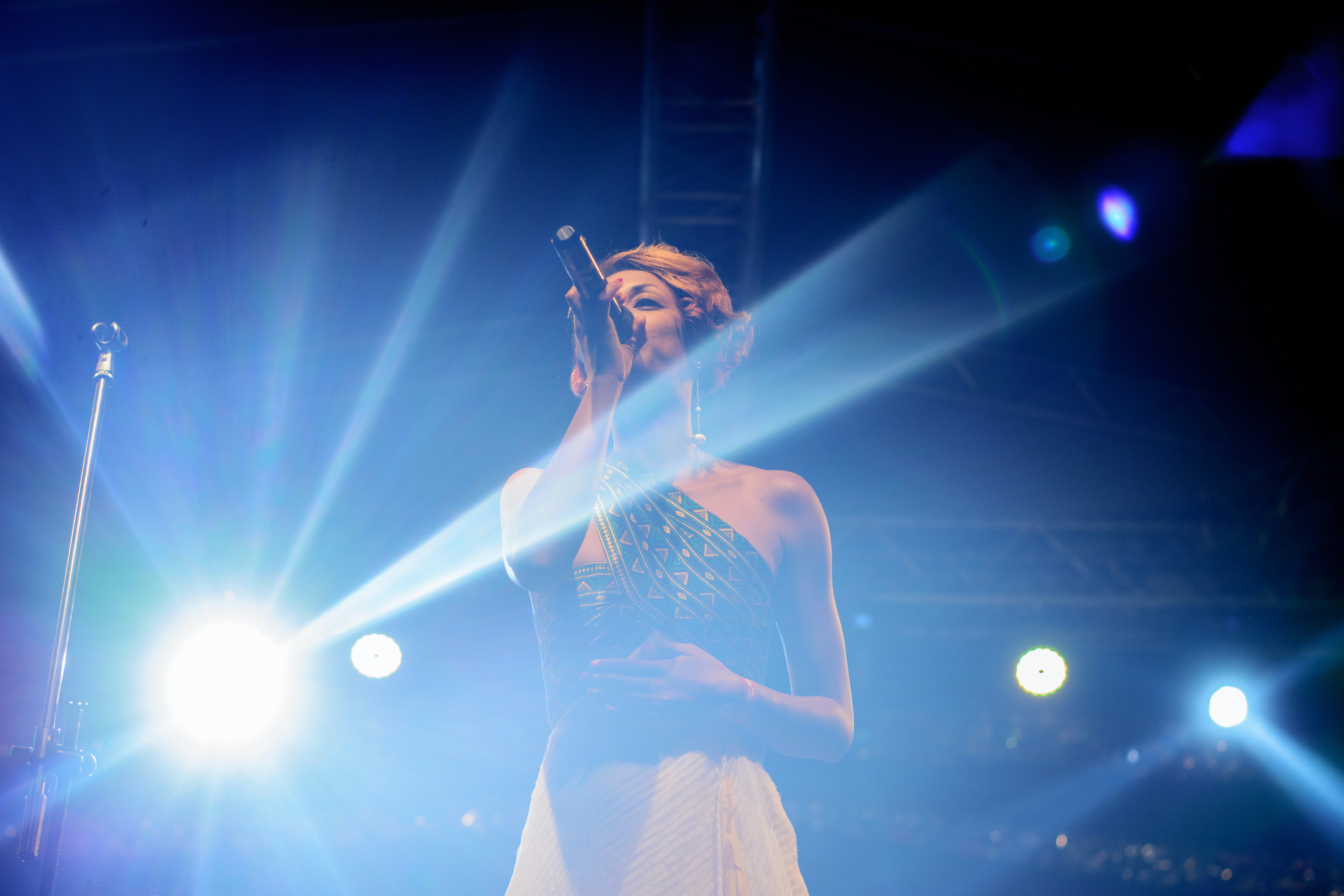 Person Wearing Black One-shoulder Top and Beige Skirt Holding Microphone