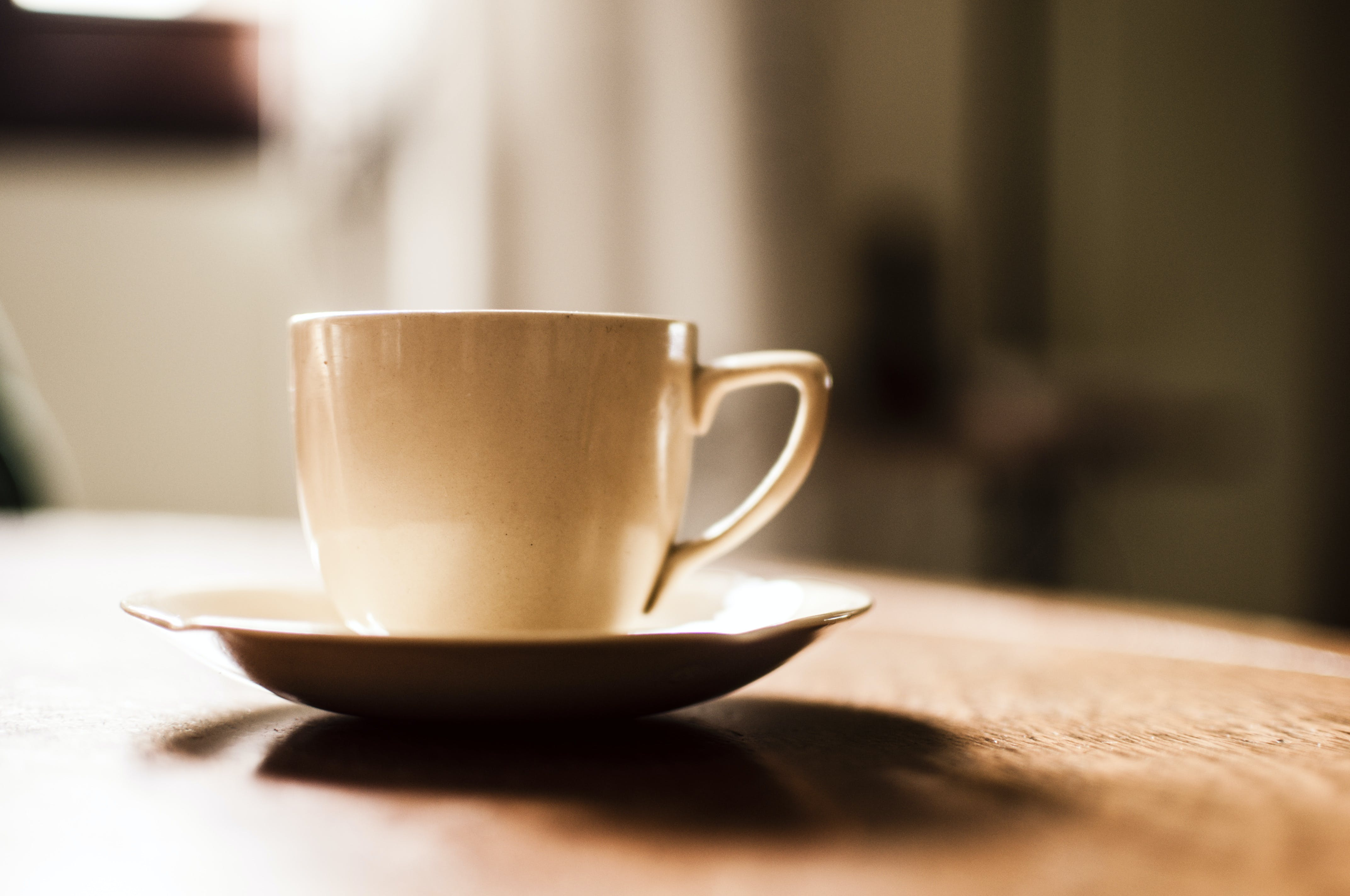 White Ceramic Teacup With Saucer on Wooden Table
