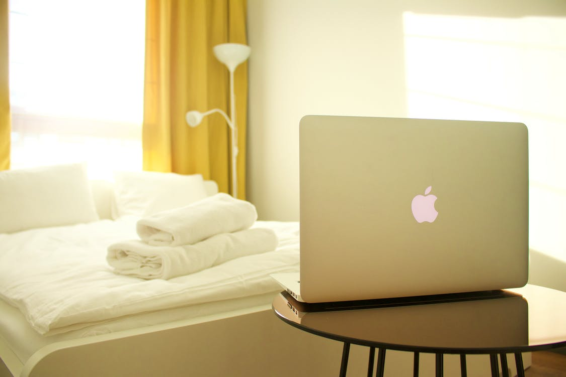 Macbook Air on Top of Wooden Table Facing White Bed