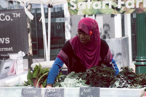 Woman With Purple Hijab Standing in Front of Vegetables