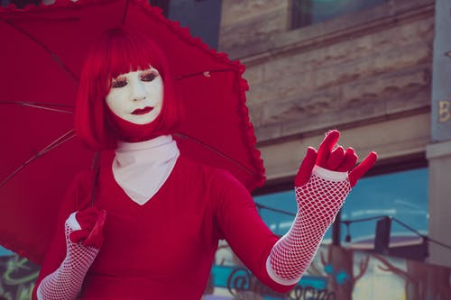 Woman Wearing Red Long-sleeved Shirt and Red Wig While Holding Red Umbrella