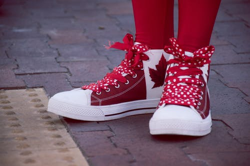 Closeup Photo of Person Wearing White-and-red Maple Leaf-printed Lace-up Sneakers