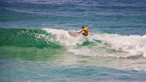 Man in Yellow Shirt Surfing
