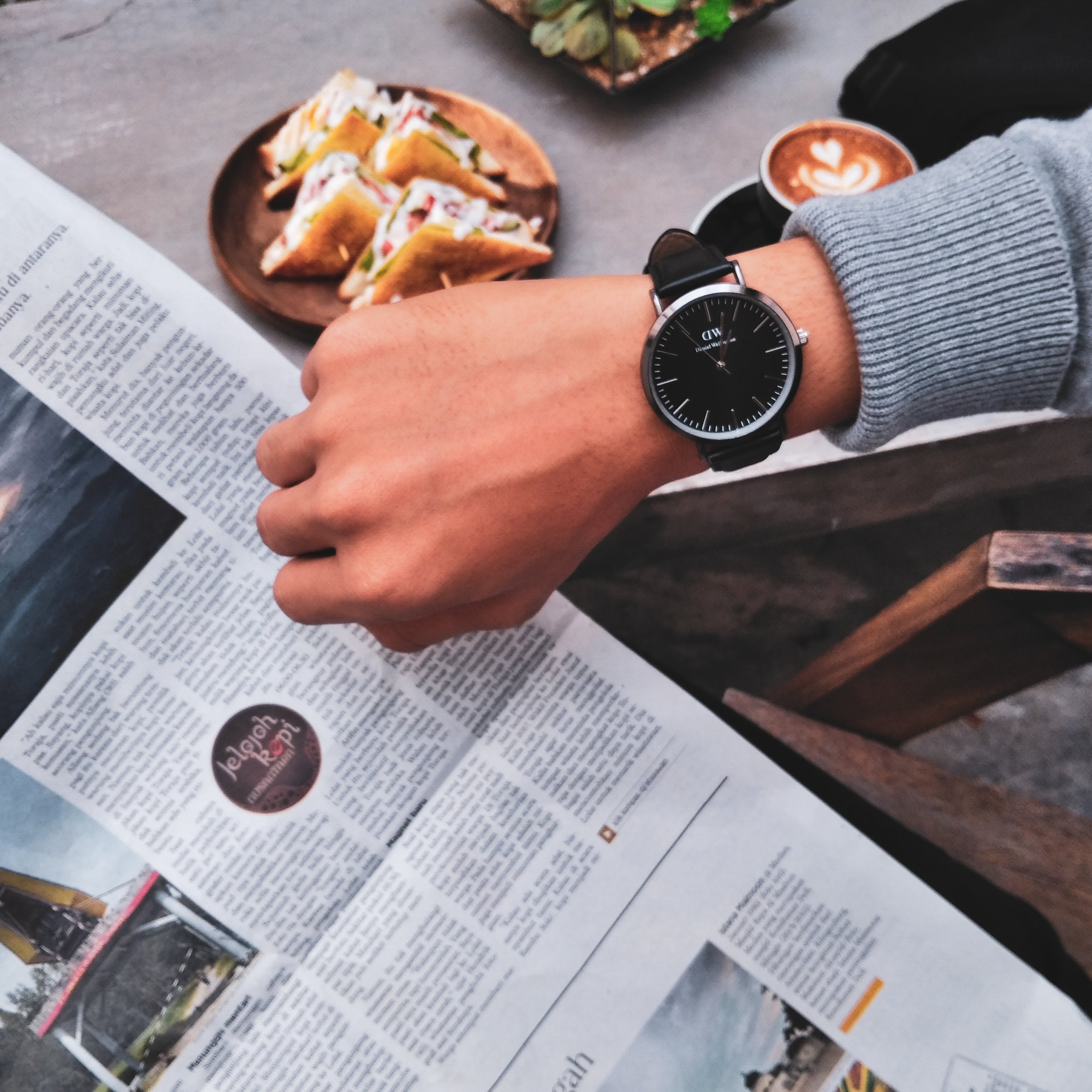 Person Wearing Watch Near the Newspaper