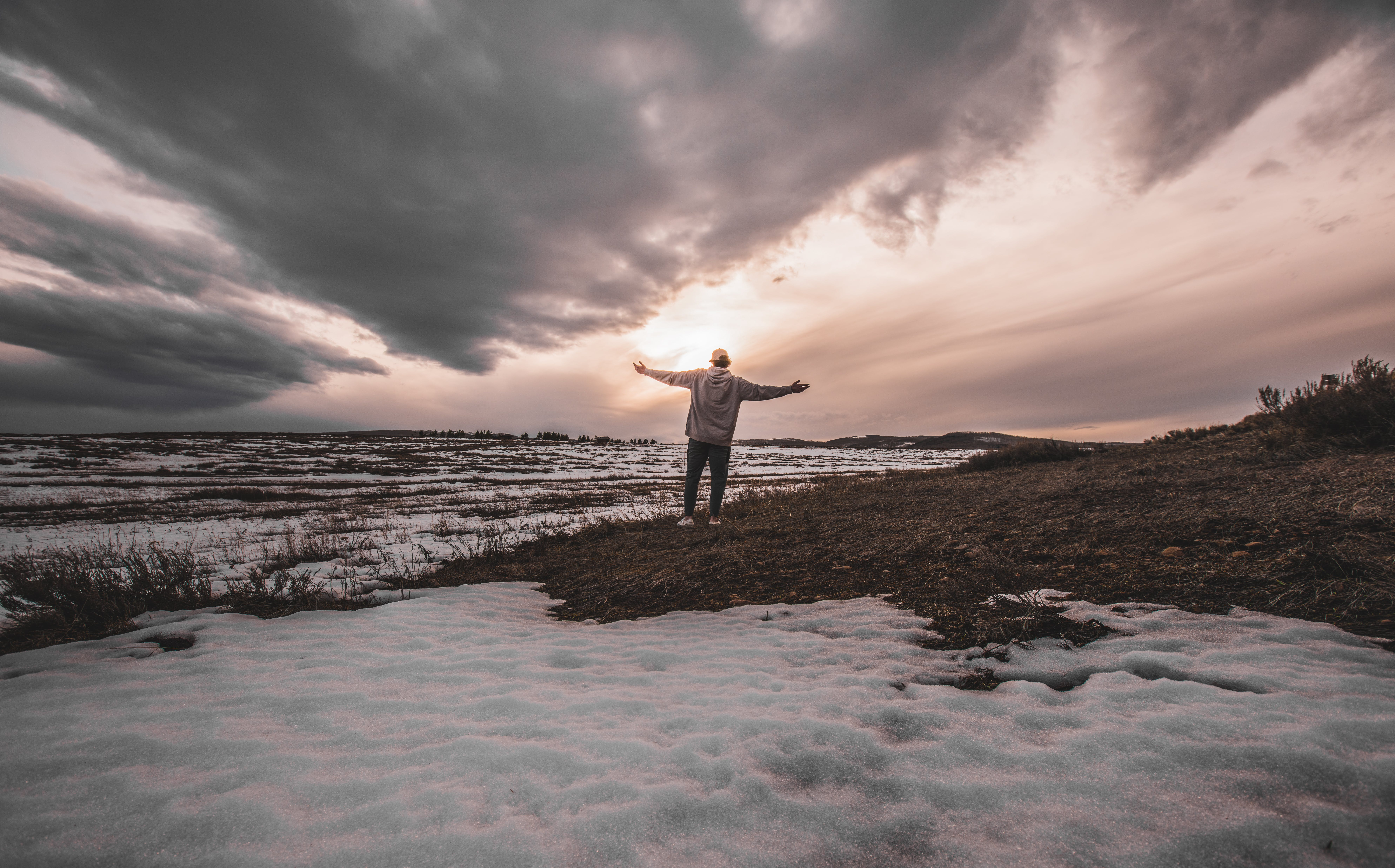 Person Standing on Snowy Field
