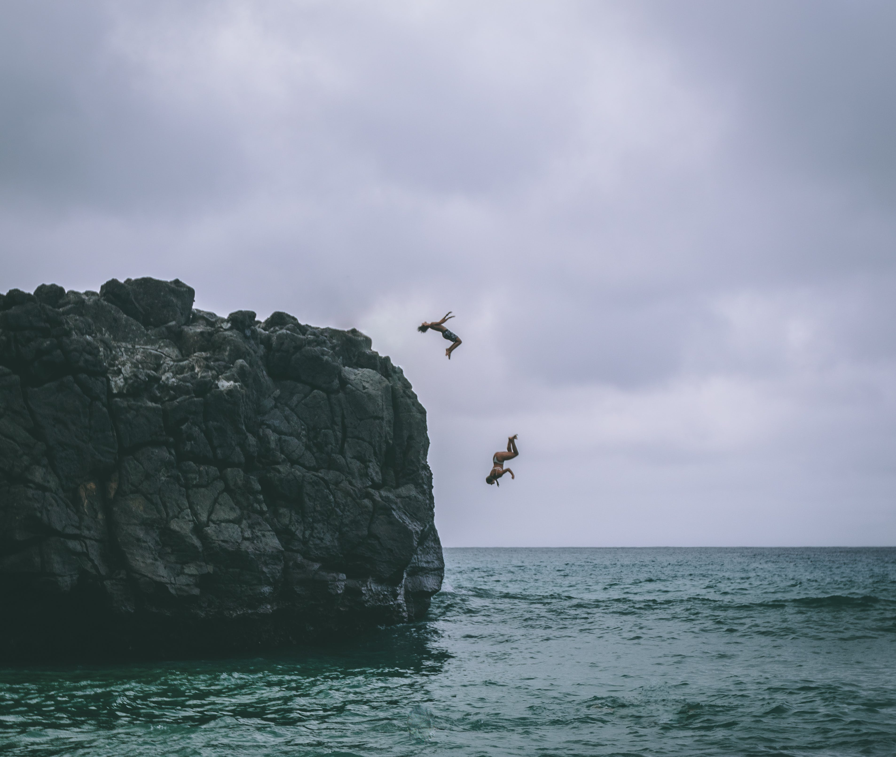 Two People Jumping on Body of Water