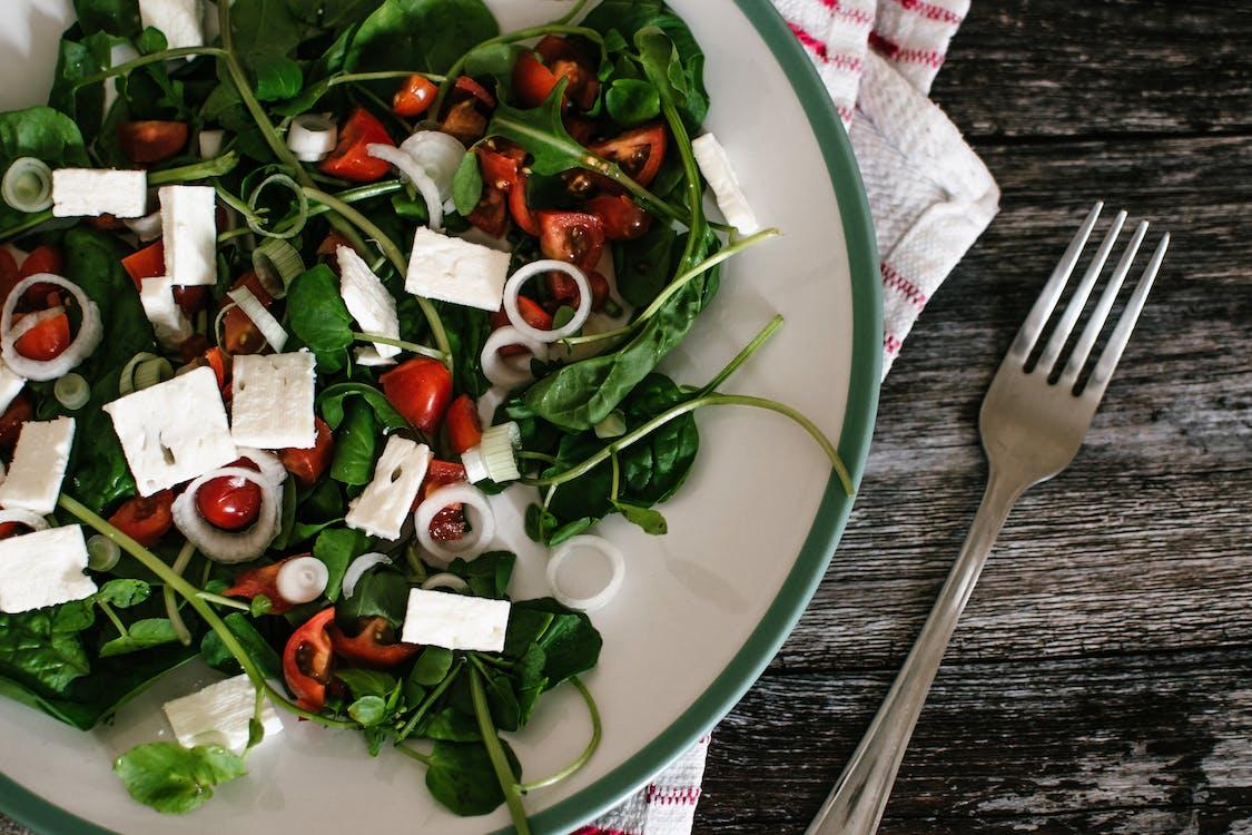 cà chua, rau chân vịt, cheese để trong đĩa, trên bàn gỗ có 1 cái khăn và dĩa