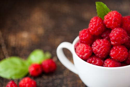 Ripe Raspberries in White Teacup in Tilt Shift Photography