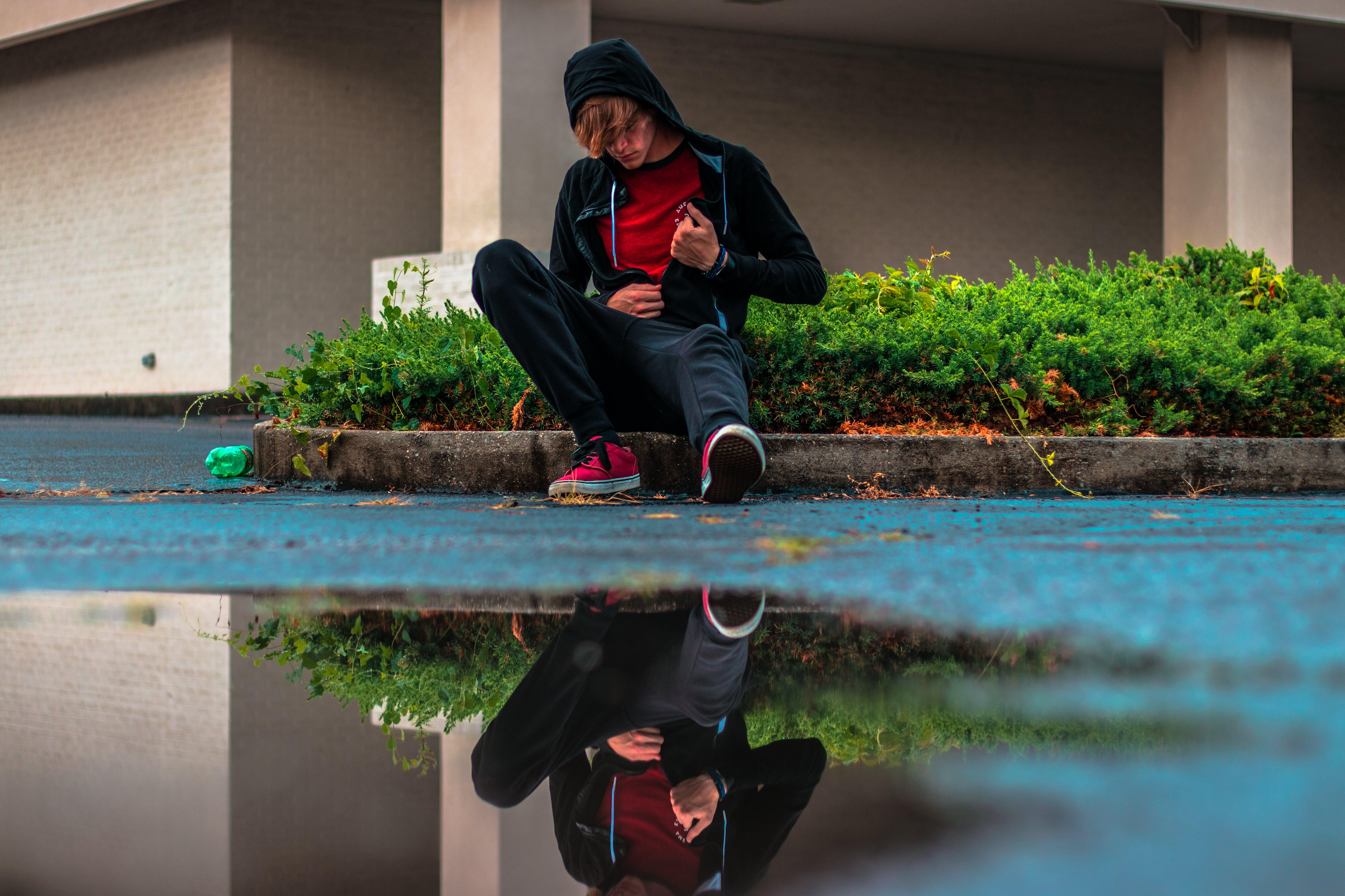 Boy Sitting on Gray Concrete Pavement