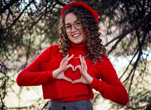 Woman in Read Long-sleeved Top Making Heart Shape Using Her Hands