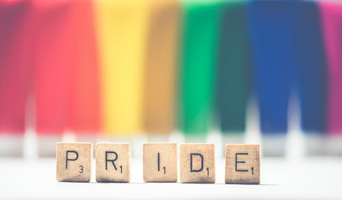 Selective Focus Photography of Scrabble Pride on White and Multicolored Background
