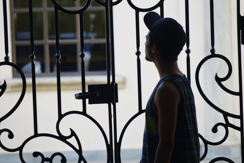 Free stock photo of boy, fence, mystery, shadow