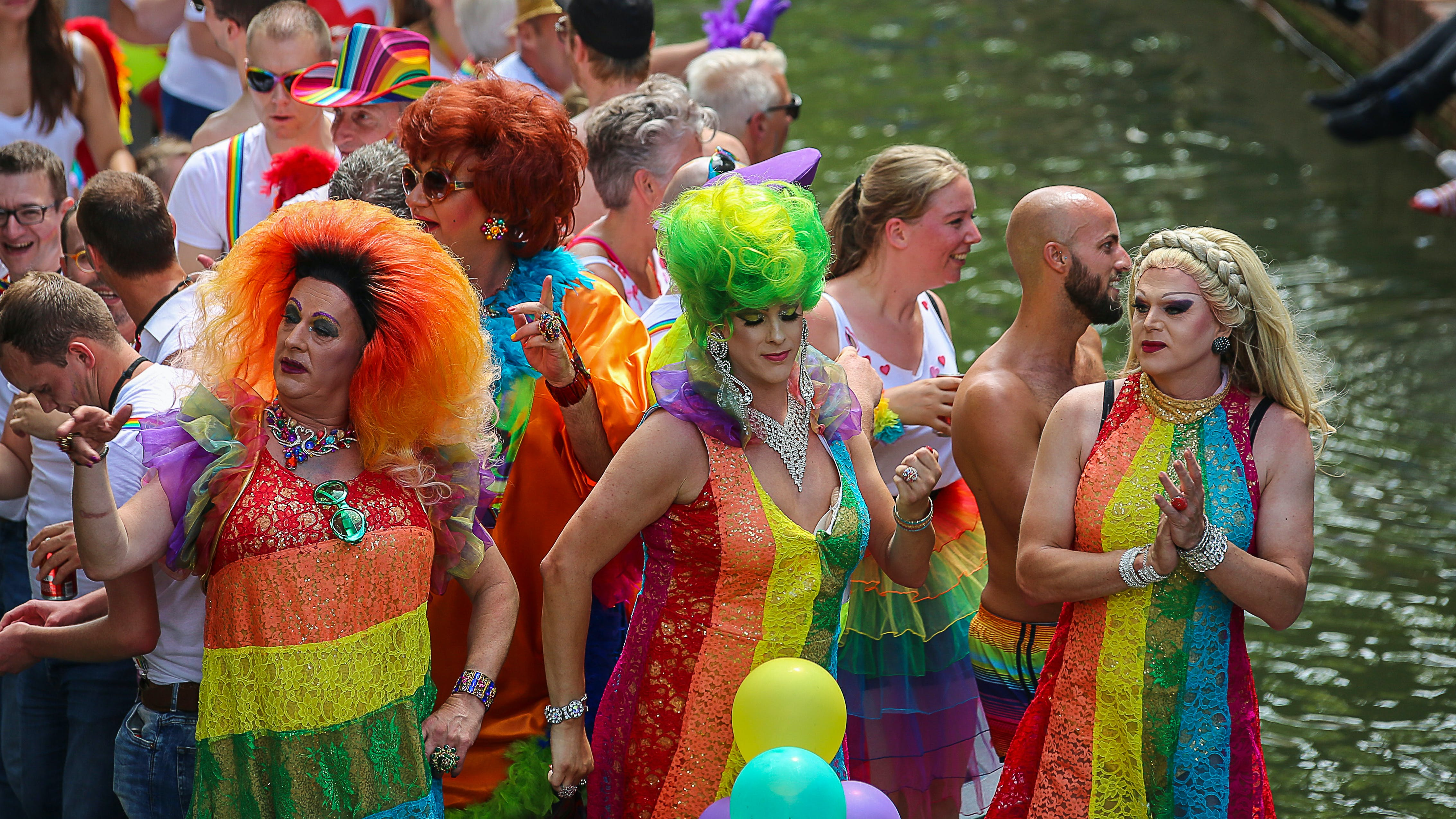 Three People Wearing Rainbow Dresses Dancing in Front of Crowd