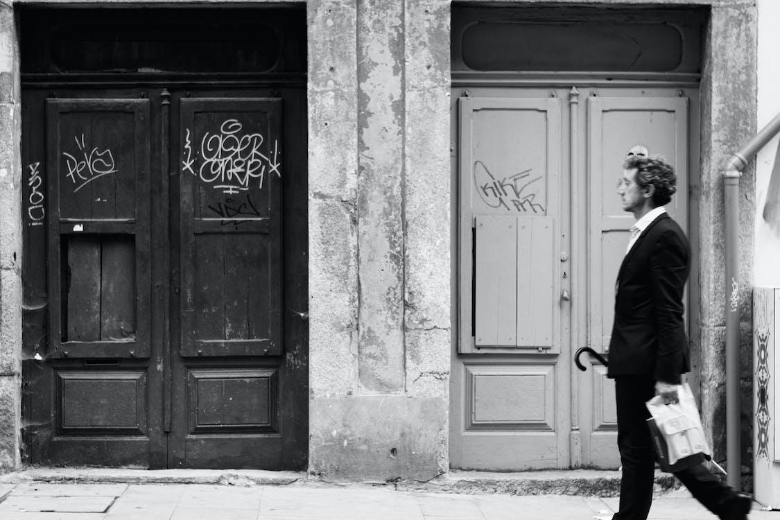Greyscale Photo of Man Walking on Street