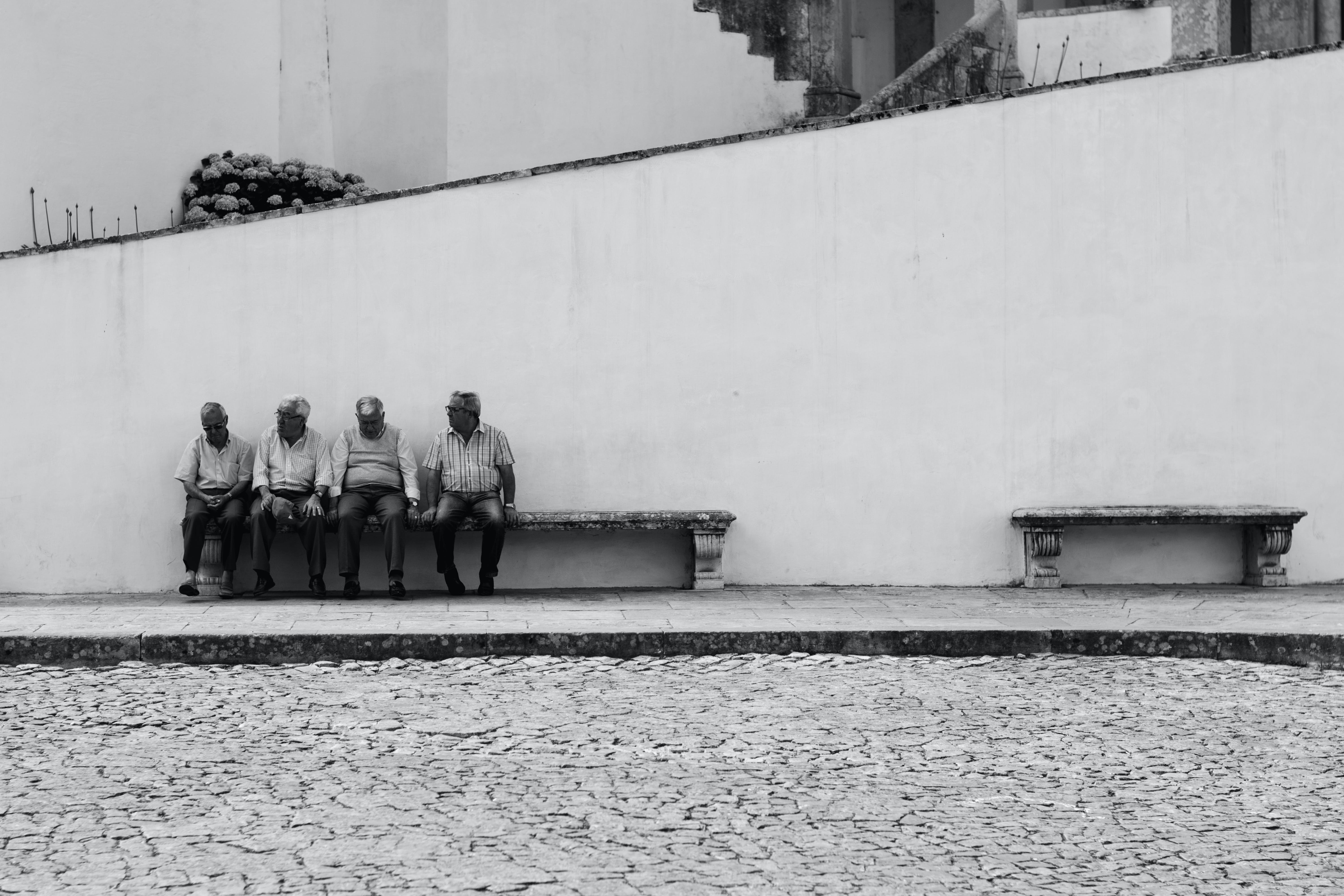 Grayscale Photo of Four Men Sitting on Bench Along the Street