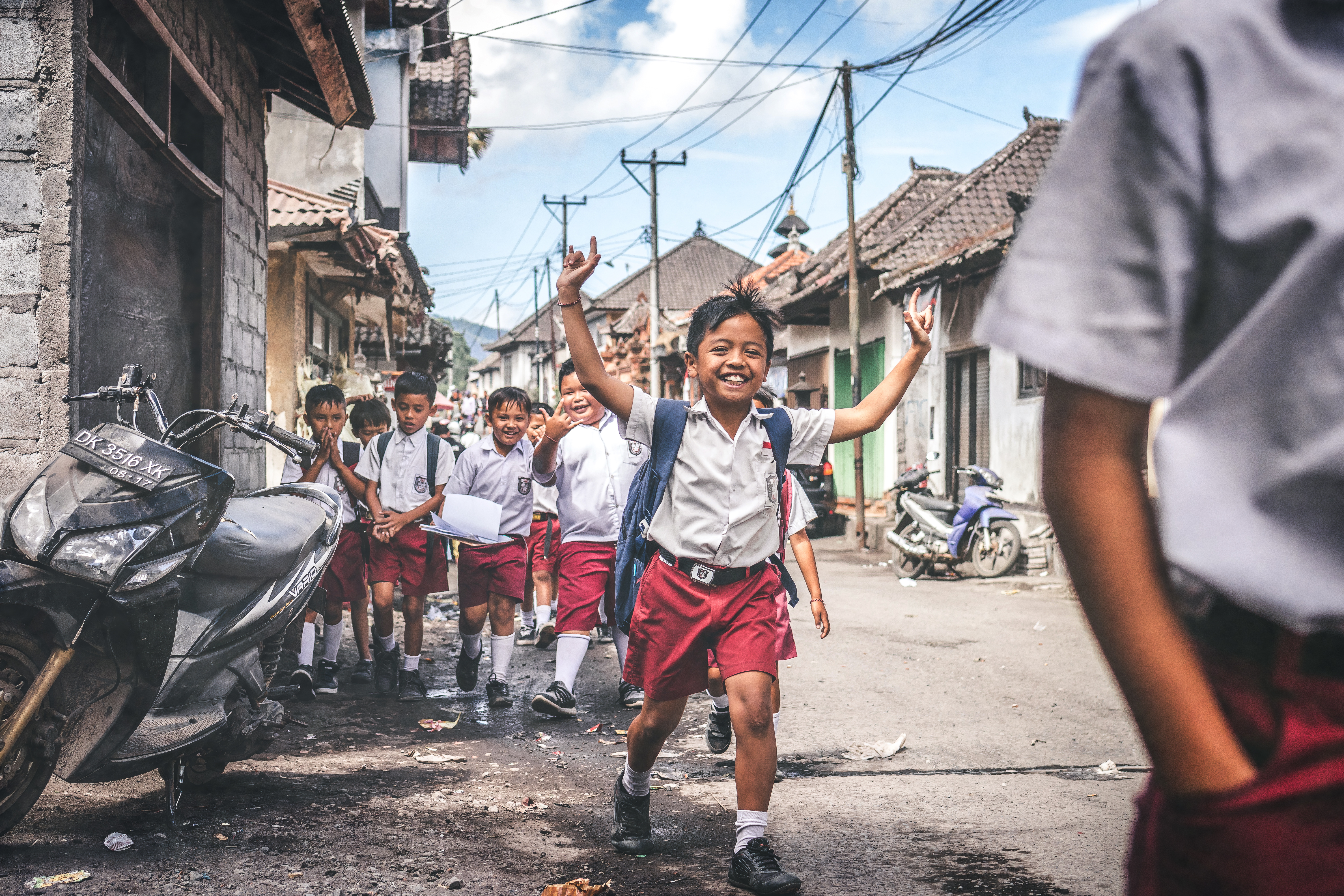 Boy in White and Red School Uniform Raising Hands Outdoors