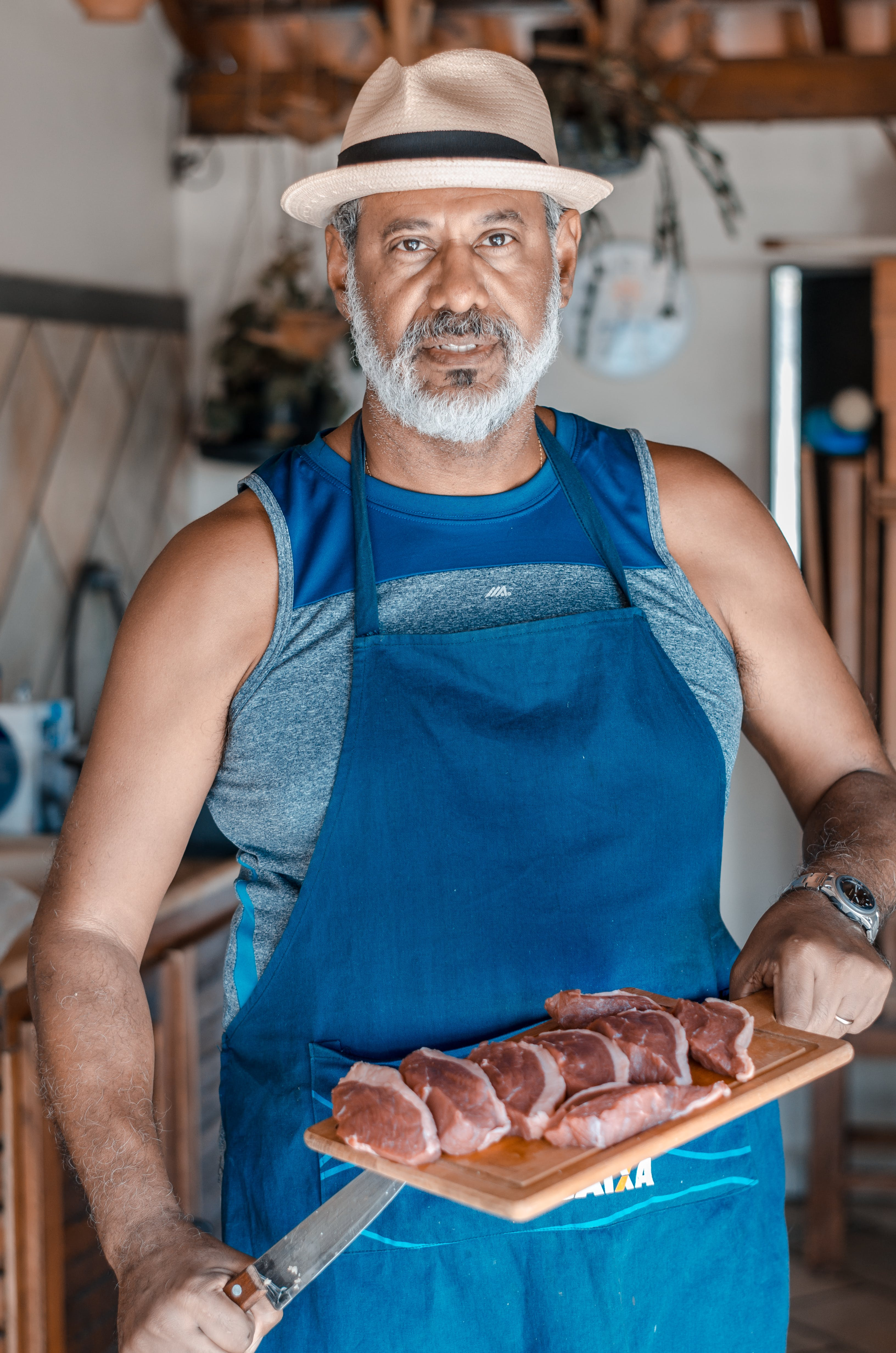 Man in Blue Kitchen Apron Holding Knife and Chopping Board With Sliced Meat