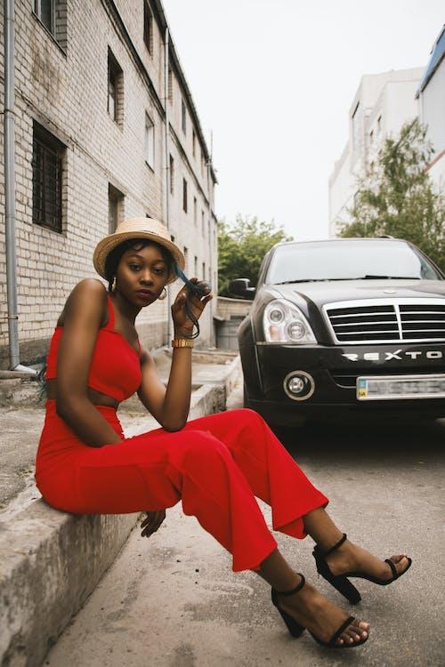 Woman Sitting on Edge Near Car