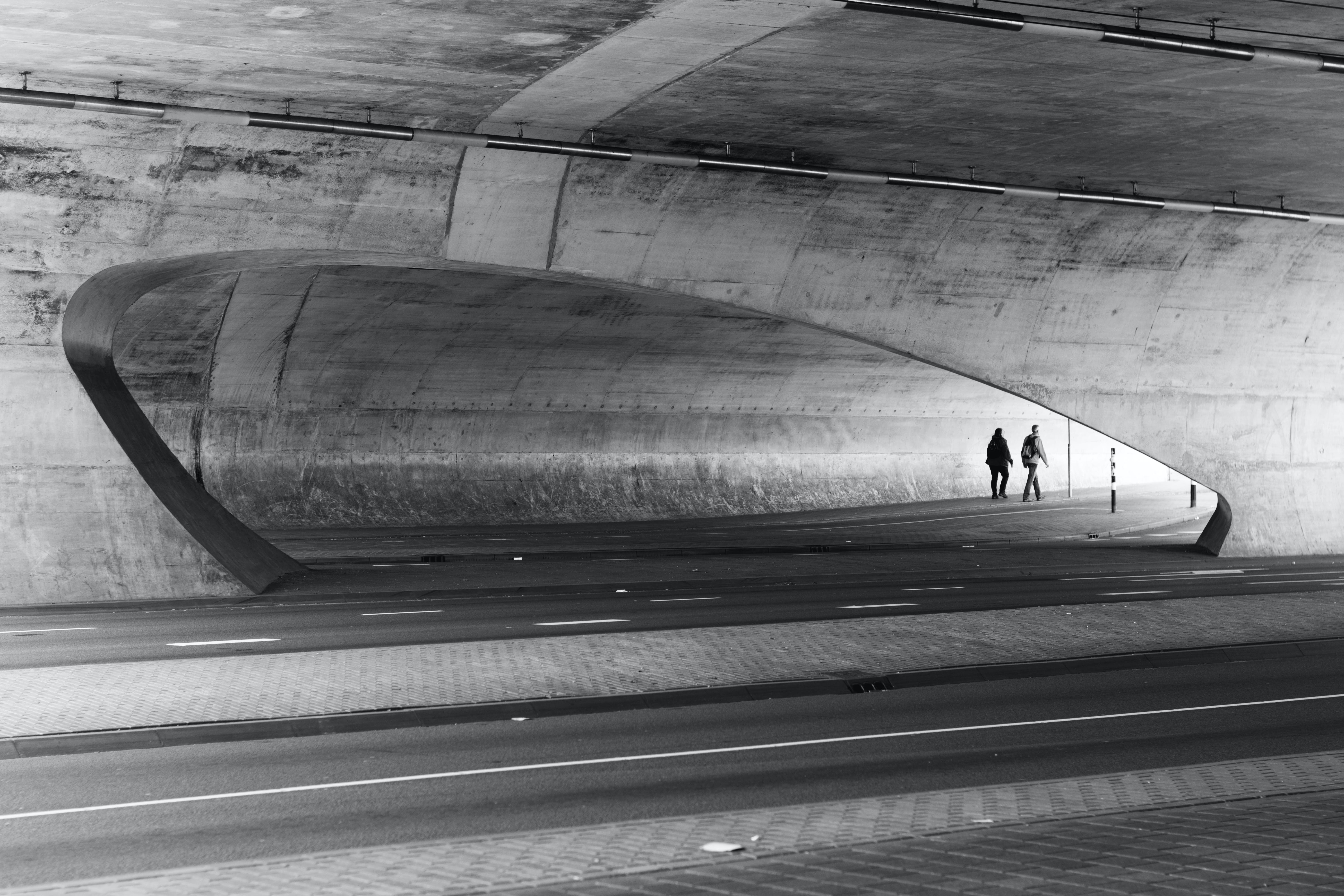 Greyscale Photography of Two People Walking Near Wall